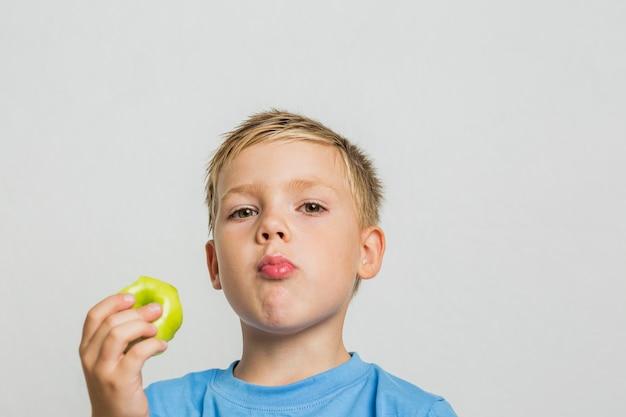 Giovane ragazzo del primo piano con una mela