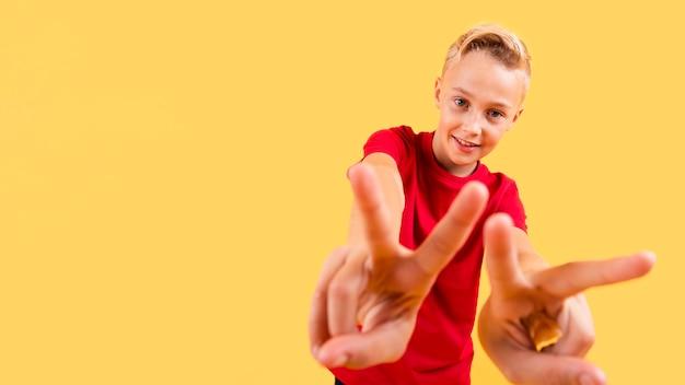 Giovane ragazzo di angolo basso che mostra il segno di pace