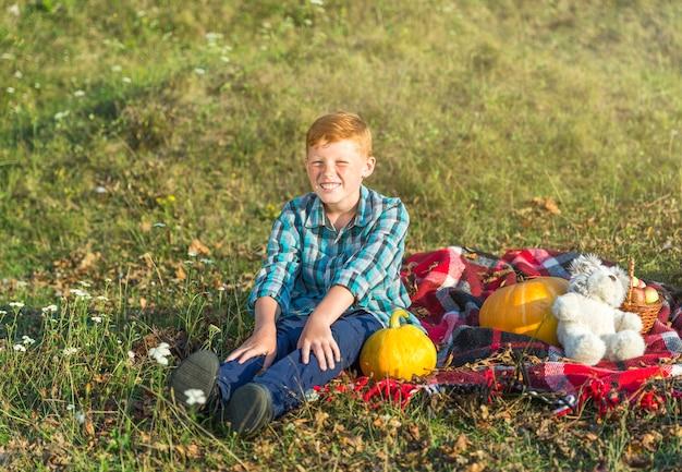 Giovane ragazzo di smiley che si siede su una coperta di picnic