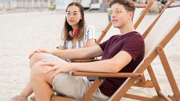 Giovane ragazzo e ragazza che si distendono insieme alla spiaggia