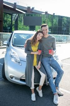 Giovane ragazzo e ragazza in piedi appoggiato su una macchina
