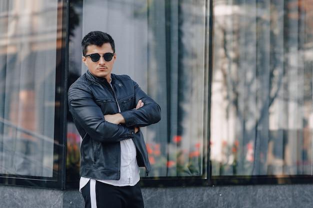 Giovane ragazzo elegante con gli occhiali in giacca di pelle nera