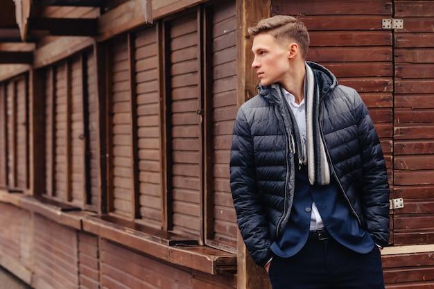 Giovane ragazzo elegante con una faccia monumentale cammina in una città fresca vicino alle mura in legno e pietra