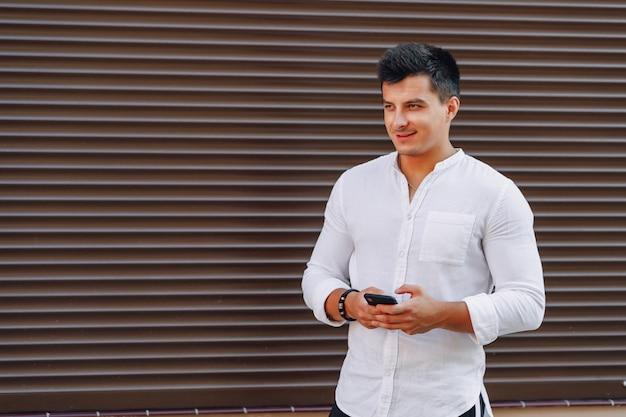 Giovane ragazzo elegante in camicia digitando sul telefono
