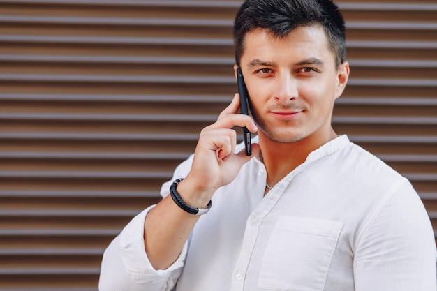 Giovane ragazzo elegante in camicia parlando al telefono