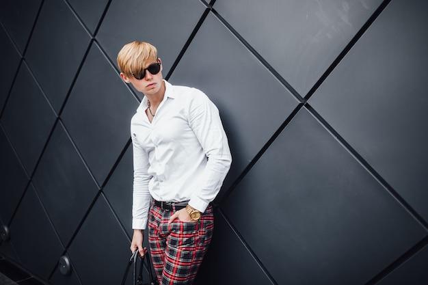 Giovane ragazzo elegante sullo sfondo di un muro nero