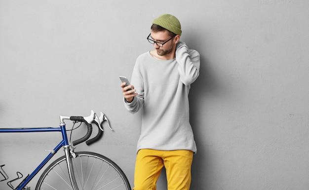 Giovane ragazzo europeo non rasato che indossa occhiali alla moda e cappello che toccano il collo mentre legge importanti notizie o messaggi di testo su smart phone generico, in piedi al muro grigio con bici ad ingranaggi fissi