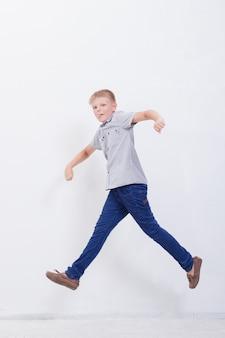 Giovane ragazzo felice che salta sul bianco