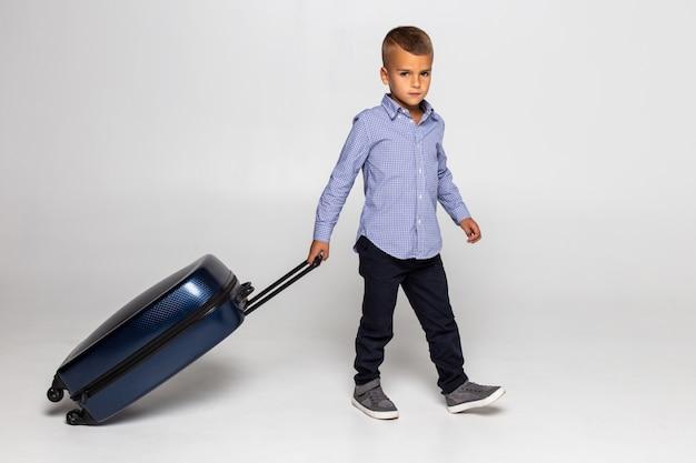 Giovane ragazzo felice che si siede dietro la valigia nera isolata sopra la parete bianca.