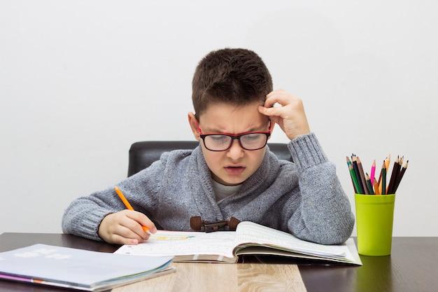 Giovane ragazzo frustrato per i compiti, scrivendo a casa. ragazzo, studiare, tavola. disegno del bambino con una matita.