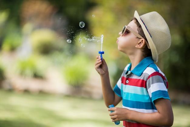Giovane ragazzo in occhiali da sole che soffia bolle attraverso la bacchetta della bolla