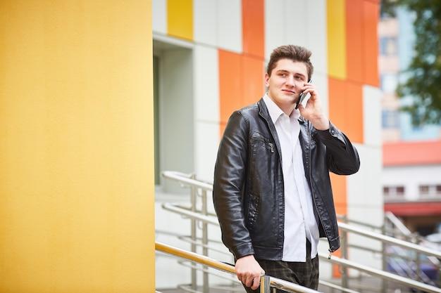 Giovane ragazzo in una giacca di pelle a parlare su un telefono cellulare, mentre in piedi sulle scale.