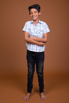 Giovane ragazzo indiano che indossa la camicia a scacchi su sfondo marrone