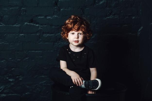 Giovane ragazzo riccio sveglio in abbigliamento casual scuro che si siede con le gambe attraversate