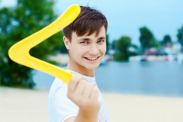 Giovane ragazzo sorridente attivo bello felice dell'uomo che gioca il gioco del boomerang delle oscillazioni sulla sabbia