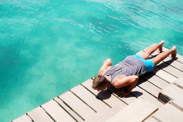 Giovane ragazzo sportivo facendo push up in riva al mare.