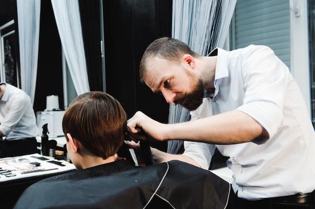 Giovane ragazzo sveglio che ottiene un taglio di capelli in un salone