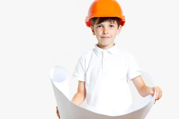Giovane ragazzo sveglio con il casco di sicurezza