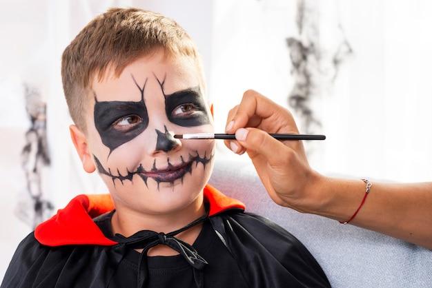 Giovane ragazzo sveglio con trucco di halloween