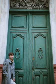 Giovane ragazzo vicino a una grande porta d'ingresso