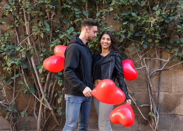 Giovane ragazzo vicino signora sorridente che tiene palloncini a forma di cuori