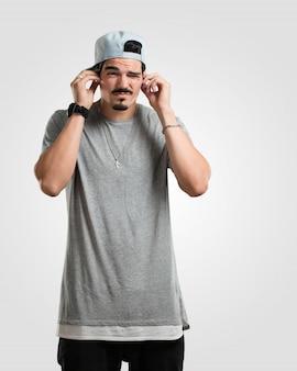 Giovane rapper uomo che copre le orecchie con le mani, arrabbiato e stanco di sentire un po 'di suono