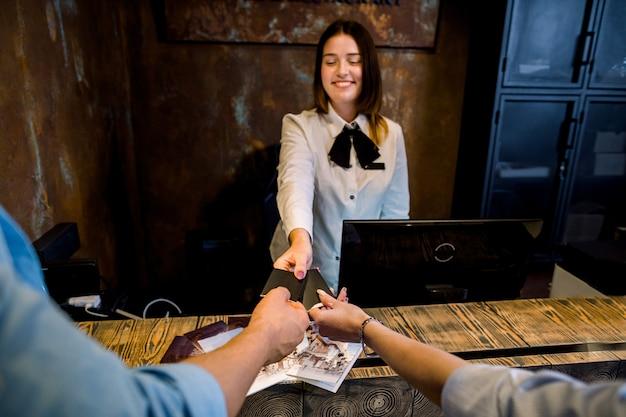 Giovane receptionist femminile sorridente che fornisce le carte chiave ai nuovi ospiti all'hotel.