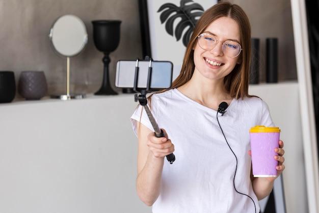 Giovane registrazione di blogger con lo smartphone che tiene una tazza di viaggio