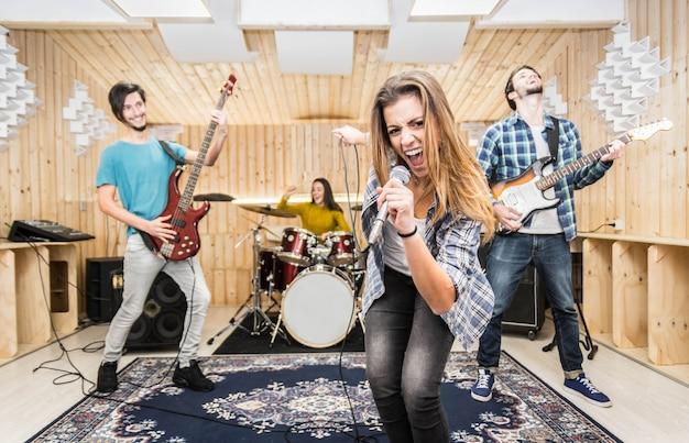 Giovane registrazione di musica di gruppo in uno studio.