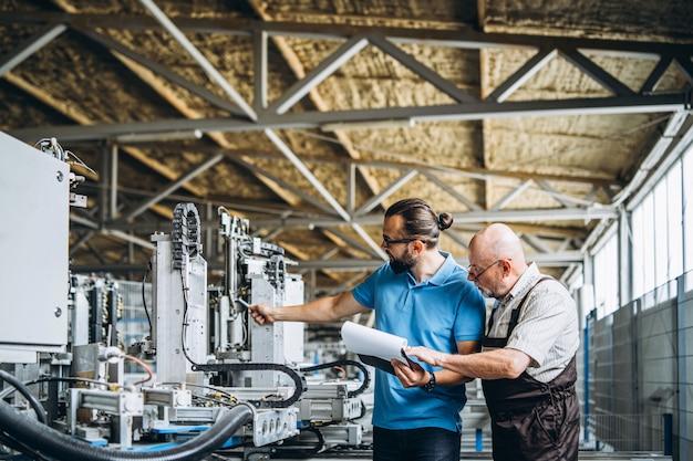 Giovane responsabile con la barba che mostra e che controlla processo di lavoro del lavoratore professionista adulto sulla grande fabbrica.