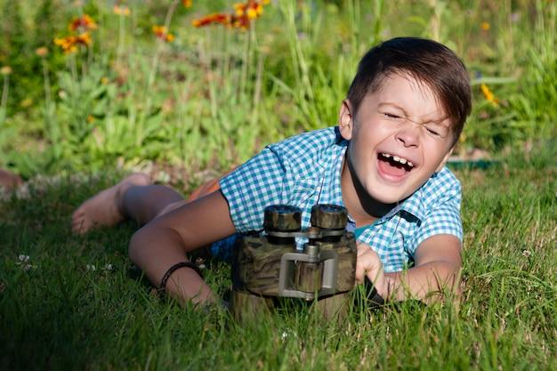 Giovane ricercatore del ragazzo che esplora con l'ambiente del binocolo in giardino