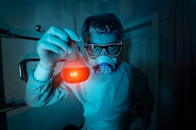 Giovane ricercatore maschio che effettua esperimento scientifico.