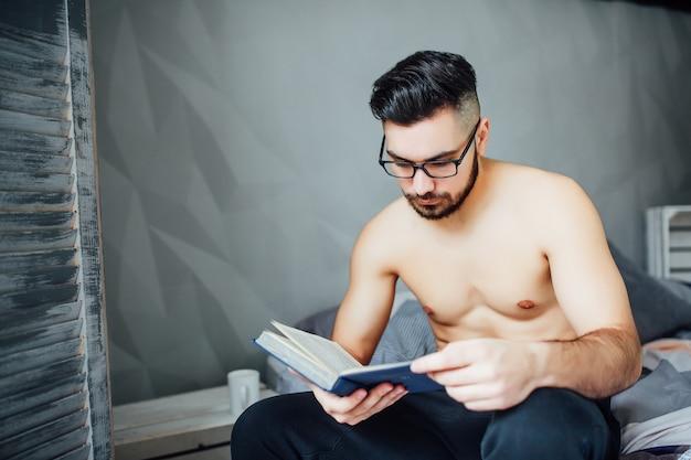 Giovane rilassato che legge un libro interessante mentre trovandosi a letto a casa