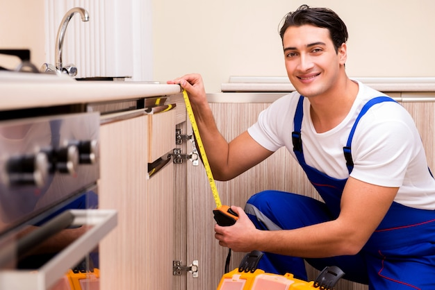 Giovane riparatore che lavora alla cucina