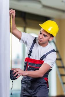 Giovane riparatore con la misura di nastro che lavora alle riparazioni
