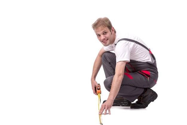 Giovane riparatore con la misura di nastro isolata su bianco
