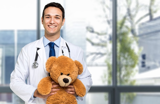 Giovane ritratto bello del pediatra che tiene un orsacchiotto