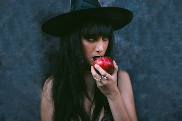 Giovane ritratto della donna della strega di halloween che mangia una mela rossa. beauty angry vampire strega con la bocca nera nell'oscurità, indossa un cappello da strega.