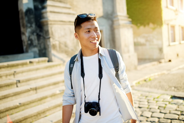 Giovane ritratto di viaggio asiatico di viaggiatore con zaino e sacco a pelo nella città.