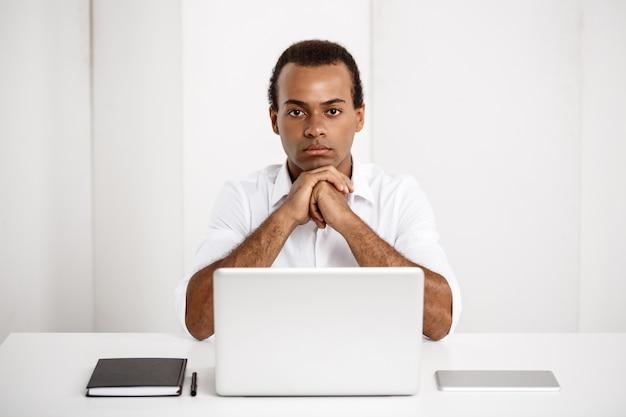 Giovane riuscito uomo d'affari che si siede nel luogo di lavoro con il computer portatile