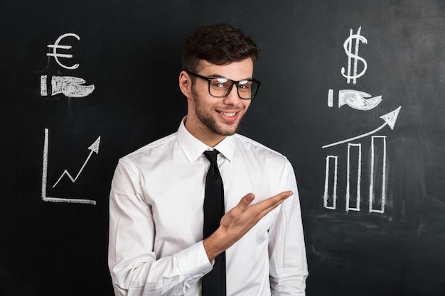 Giovane riuscito uomo in camicia bianca che presenta nuovo progetto finanziario
