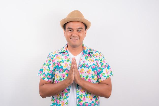 Giovane saluto asiatico dell'uomo con la cultura tailandese