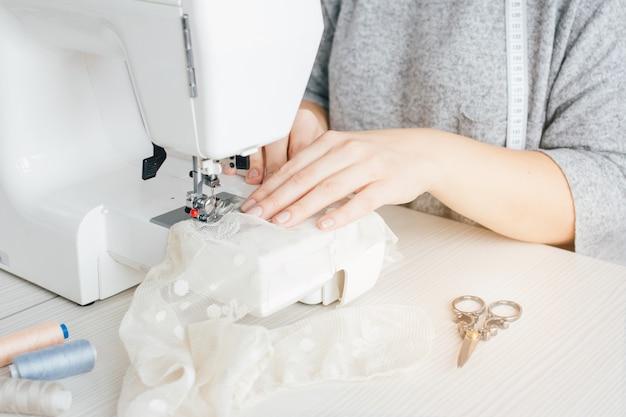 Giovane sarta che lavora alla macchina per cucire