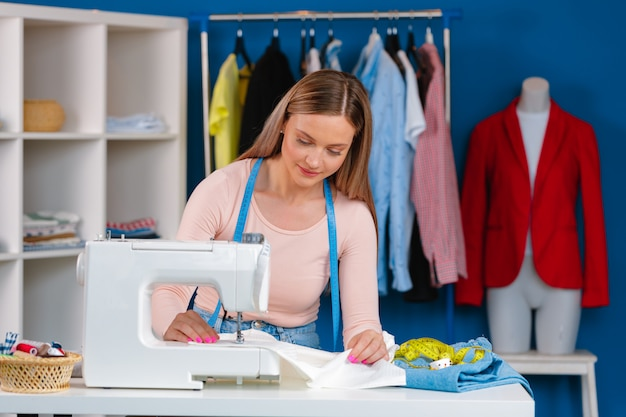 Giovane sarta che lavora alla sua macchina per cucire sulla fabbrica tessile