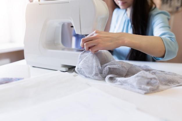 Giovane sarta con macchina da cucire che lavora nel suo ufficio. concetto di piccola impresa