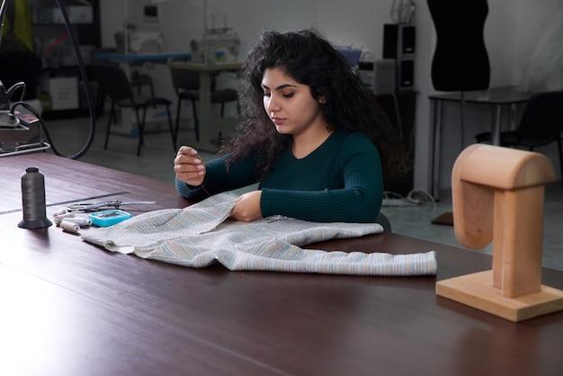 Giovane sarta giacca da cucito in studio mentre era seduto al suo posto di lavoro