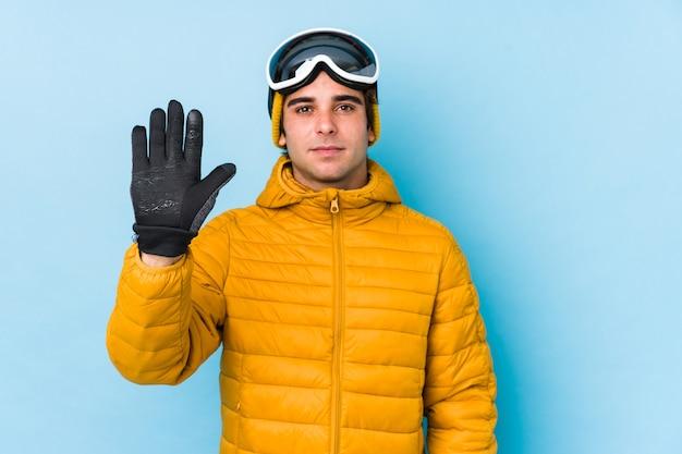 Giovane sciatore che indossa occhiali da snowboard isolato in piedi con la mano tesa che mostra il segnale di stop, impedendoti.