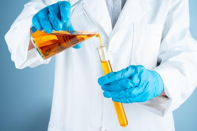 Giovane scienziato con la provetta che effettua ricerca in laboratorio clinico.