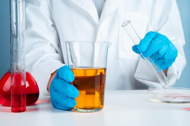 Giovane scienziato con la provetta che fa ricerca nel laboratorio clinico. specialista in scienze professionali sul lavoro.