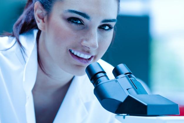 Giovane scienziato in posa con un microscopio